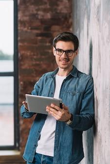 手にデジタルタブレットを持っている壁に傾いている笑顔の若い男