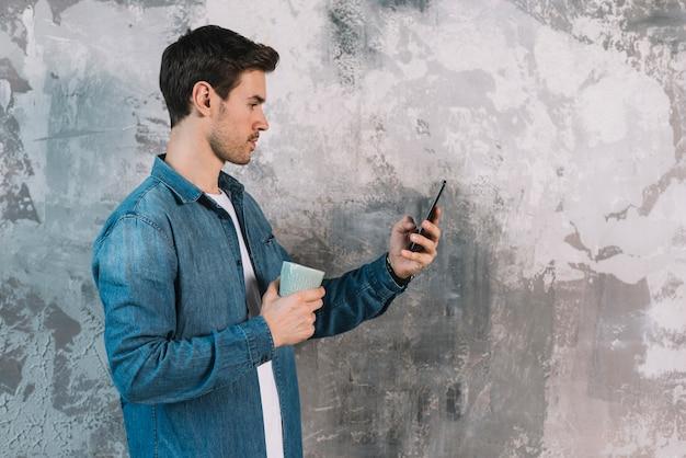 コーヒーカップを持っている携帯電話を見て風通しの壁の前に立っている若い男