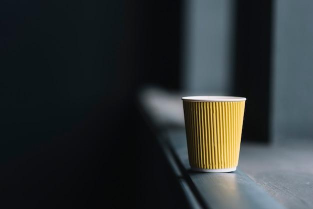 窓の敷居の端にある使い捨てコーヒーカップ
