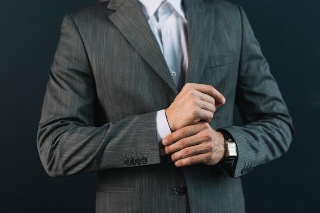 彼の袖を調整するスーツの若い男の中央部