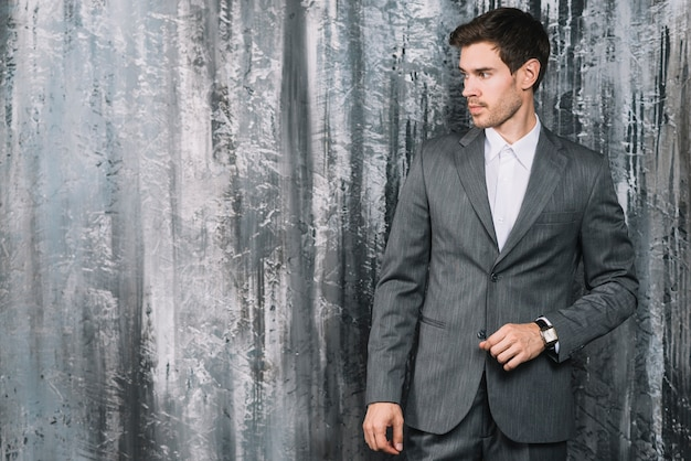 スタイリッシュな若いビジネスマンは、壁紙の前に立って