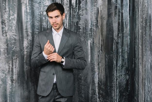 壁紙の前に彼の袖の立って調整するスーツでハンサムな若い男のクローズアップ