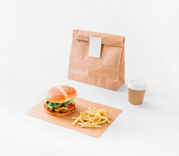 バーガー;フライドポテト;白い表面上の小包と廃棄カップ