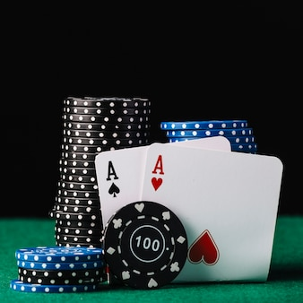 Крупный план красочных штабелированных фишек казино с сердцем и лопатой тузов на зеленом столе