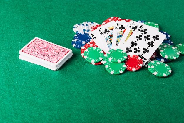 緑の火かき棒テーブルのロイヤルフラッシュカードとカジノチップ