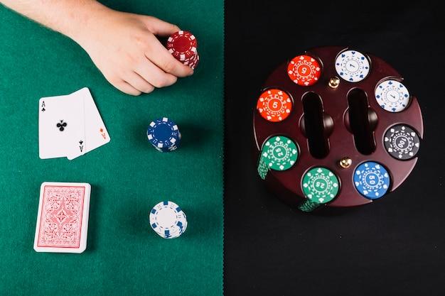 カルーセルケースにセットされたチップの近くでポーカーをしている人の高い角度のビュー