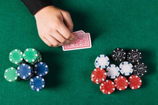ポーカーテーブルの近くでトランプを持つプレーヤーの手の高い角度のビュー