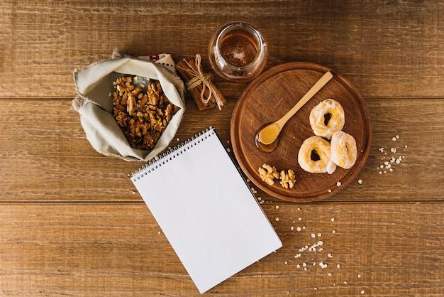 蜂蜜の高い角度のビュー;ドーナツ;クルミ;木製の机のシナモンと渦巻きのメモ帳