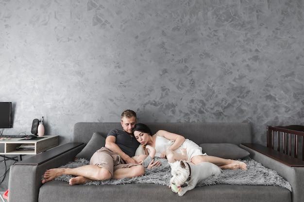 Молодая пара, любящего сына, лежащего на диване с белой собакой