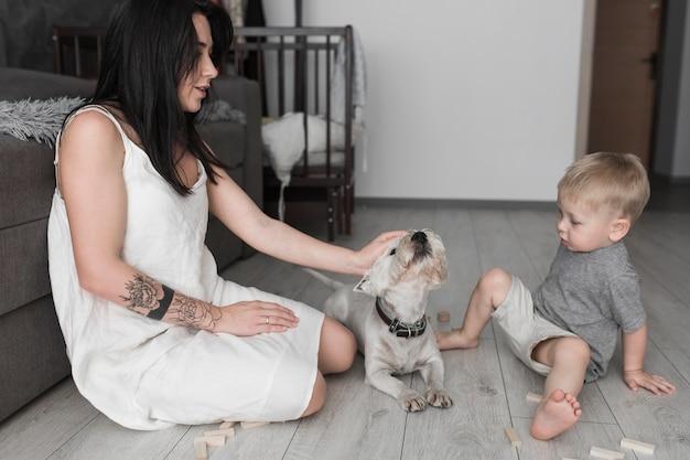 彼女の犬を愛する母親を見て小さな男の子のクローズアップ