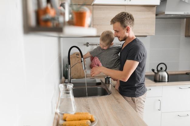 キッチン、シンクの近くに立っている彼の息子を運ぶ父親のクローズアップ