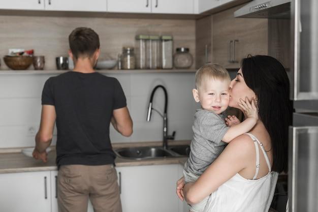 Крупный план мать, любящая сына с мужем, работающим на кухне