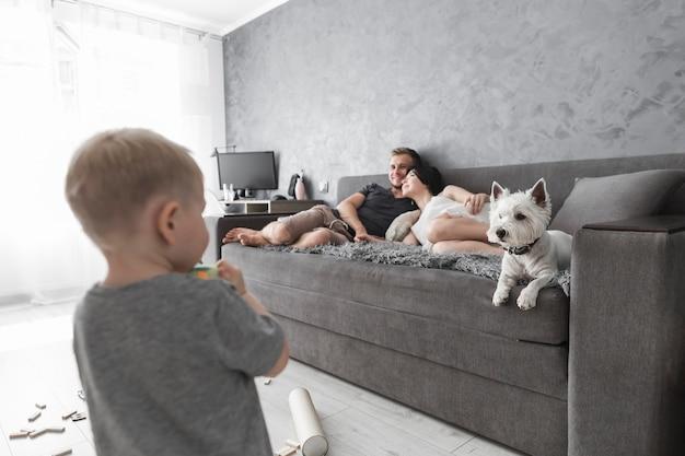 犬とソファーでリラックスした親を見ている少年の後ろ姿