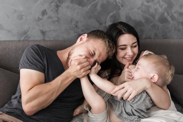 彼らの小さな息子と遊んでいるソファに座って笑顔の若いカップル