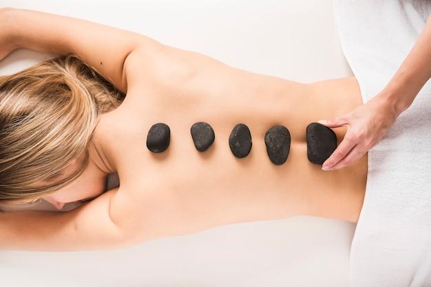 女性の背中に熱い石を置いてセラピストの手の高い角度のビュー