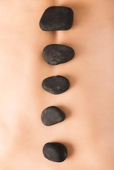 女性の背中に熱い石のマクロショット