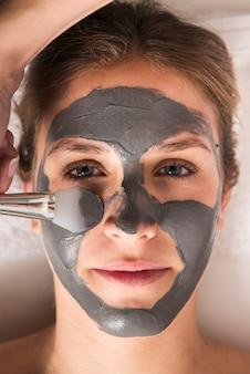 彼女の顔に顔のマスクを持つ女性のクローズアップ