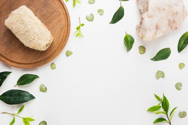 Натуральная люфа на деревянной доске со спа-камнем и разбросанными листьями на белом фоне