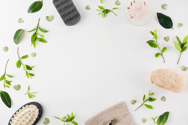 Пемза; поваренная соль; массажная щетка; натуральная люфа, украшенная зелеными листьями на белом фоне