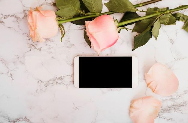 大理石のテクスチャの背景にスマートフォンを持つピンクのバラ