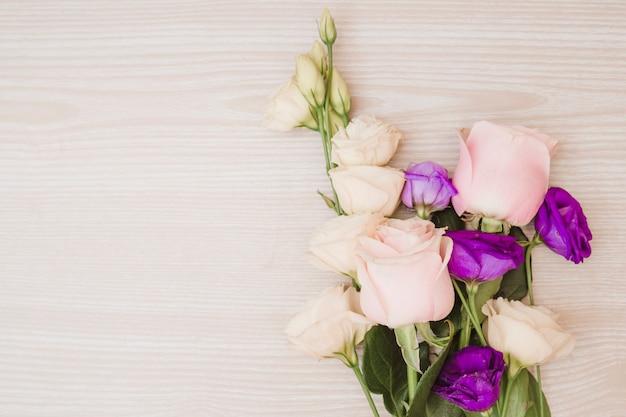 Розовые розы и фиолетовые цветы эустома на деревянном столе