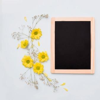 白い背景に木製の空白のスレートの近くに黄色の花の装飾