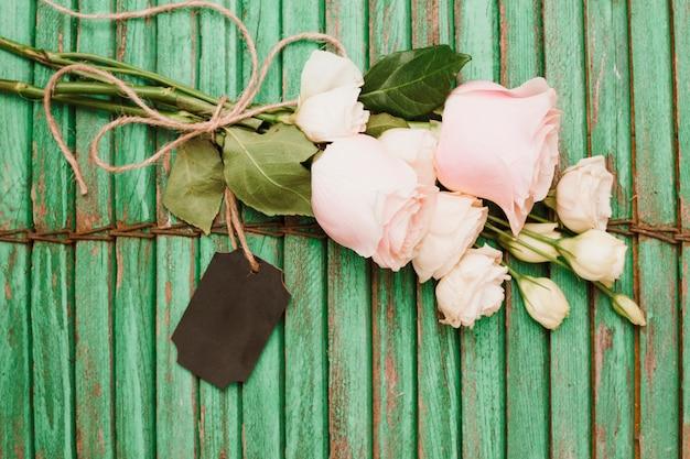 花の花束と木のシャッターの背景に紐で結ばれたタグ