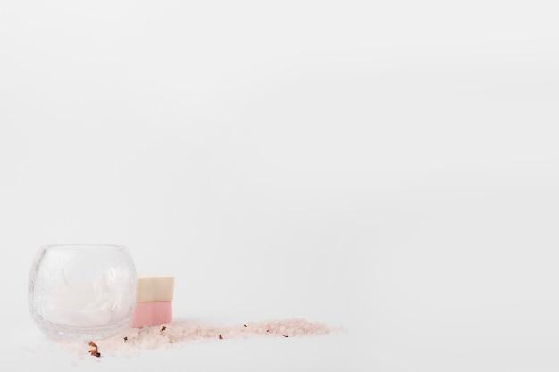 ガラスのボールのクローズアップ;スポンジ、ハーブ、塩、白、背景