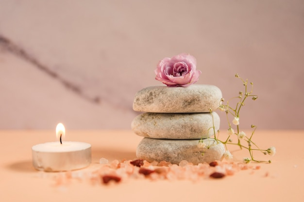 Розовая роза над стеклом камней с освещенной свечой; соли хималяна и цветы для младенца на цветном фоне