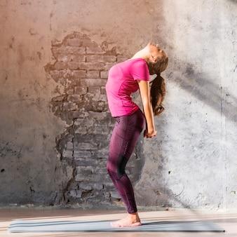 ストレッチ運動をしている若い女性の側面図
