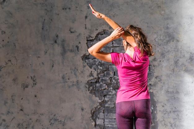彼女の腕を伸ばしている壁の前に立っている女性のクローズアップ