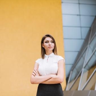 黄色の壁に立っている若いビジネスマンの肖像