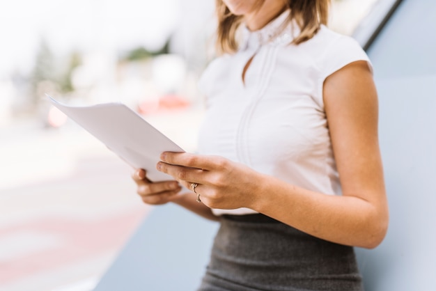 屋外で白い紙の文書を保持している事業者の中間セクション