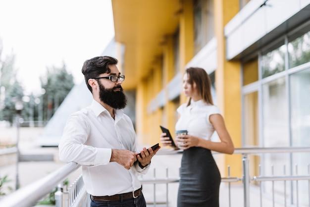 バルコニーに立っている若い実業家とビジネスマンの肖像