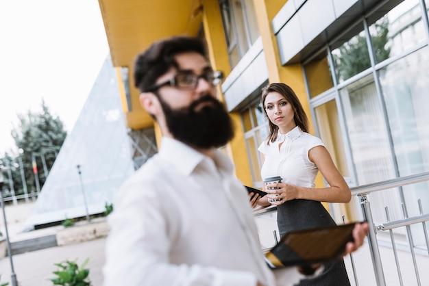 屋外での実業家の前にデジタルタブレットスタンドを保持しているビジネスマン