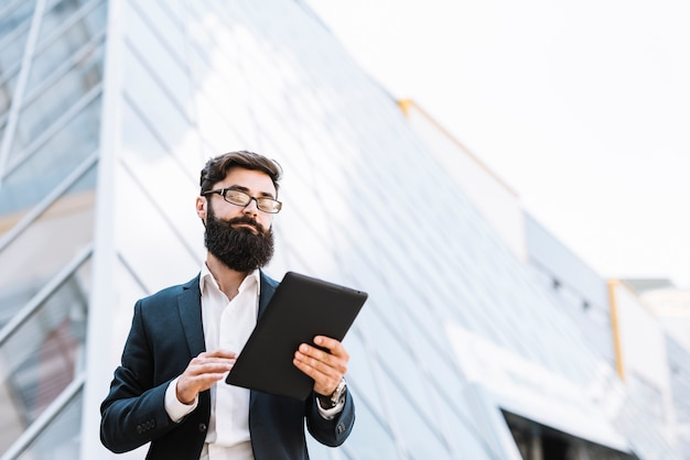 オフィスビルの外でデジタルタブレット立って見ているビジネスマンの低角度のビュー