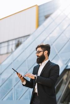 屋外でデジタルタブレットを使用してスタイリッシュな若い実業家