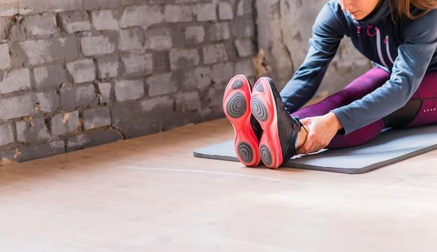 ヨガをする運動マットに座っている若い女性のクローズアップ