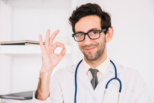 幸せな男性医者は大丈夫サインを身に着けている