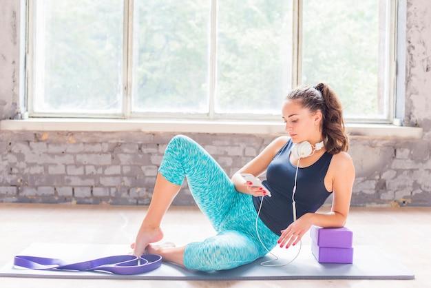 スマートフォンを使って運動マットに座っている若い女性