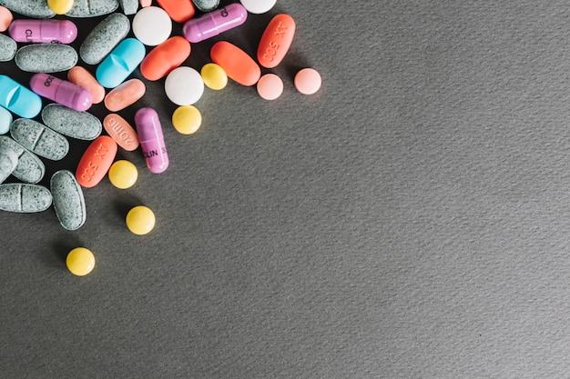 グレーの背景に様々なカラフルな丸薬の高い角度のビュー