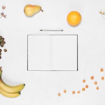 Пустой блокнот с ручкой и здоровые фрукты на белом фоне