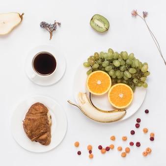 白い皿の上の果物とコーヒーで作られたスマイリーフェイス。クロワッサンとコーヒーの白い背景で隔離