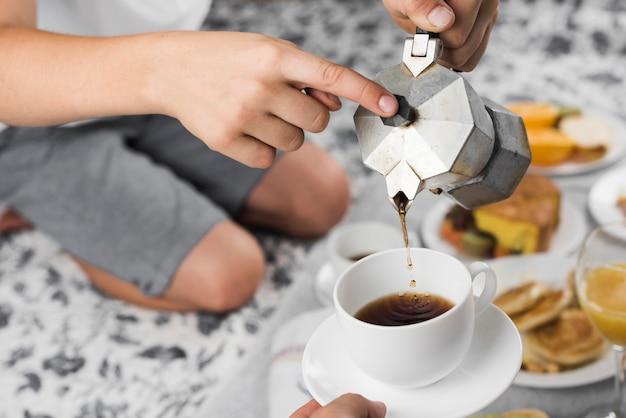 朝食に他の人のためのカップにブラックコーヒーを注ぐ少年