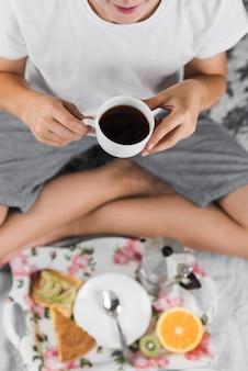 Улыбающийся мальчик держит чашку черного кофе в руке с размытым завтраком