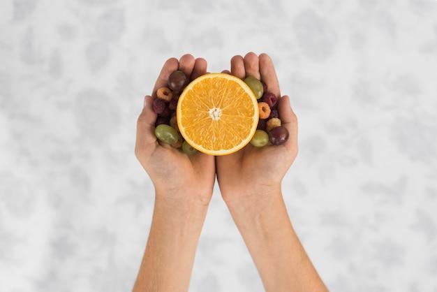 ブドウとラズベリーと半分にされたオレンジを持っている人の手のクローズアップ