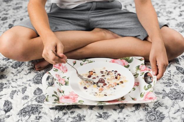 オートミールの朝食を持っているカーペットの上に座っている少年のクローズアップ