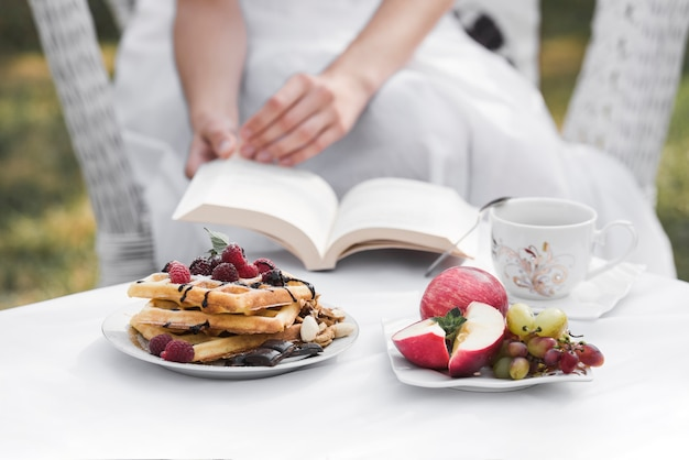 国内の庭で白いテーブルに朝食と一緒に本を手に持った女性