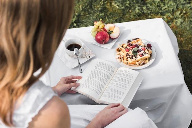 屋外のテーブルの上の朝の健康的な朝食で本を読む女の背面図