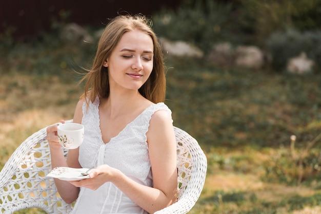 庭でコーヒーを楽しんでリラックスした笑顔金髪の若い女性